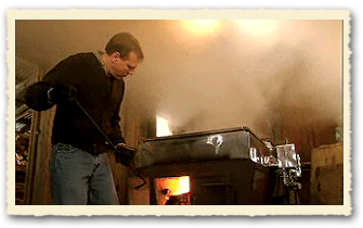 "Arnold Coombs loads the wood-fired ""arch"" or evaporator."
